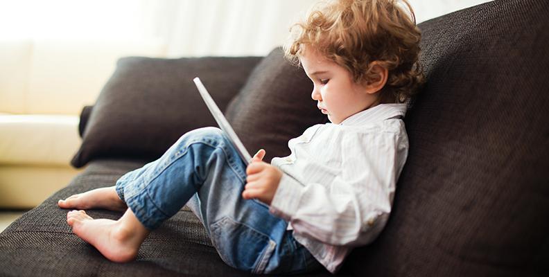 skärmtid- barn som sitter med ipad i soffan