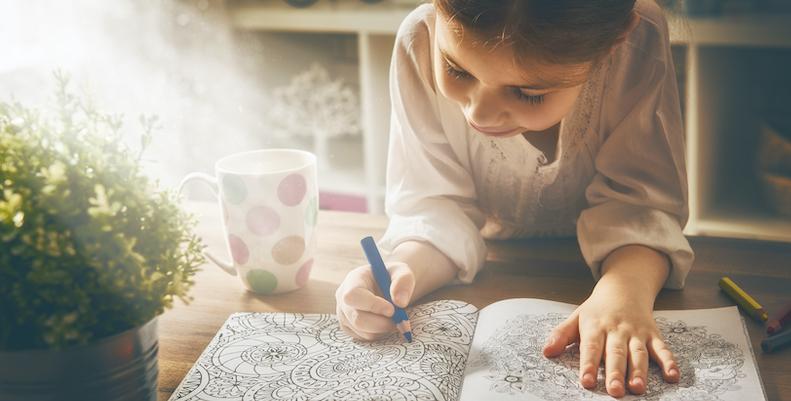 Barn som målar i färgläggningsbok. Ett kreativt sätt att hitta avslappning och samtidigt få en paus från tv eller padda.