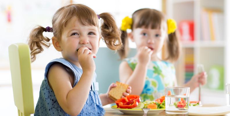 Två flickor äter god vegetarisk mat
