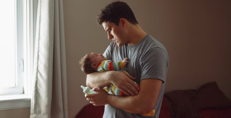 bebis blir matad med flaska av pappa