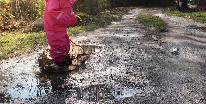 Barn i regnkläder och gummistövlar, hoppar i en lerpöl