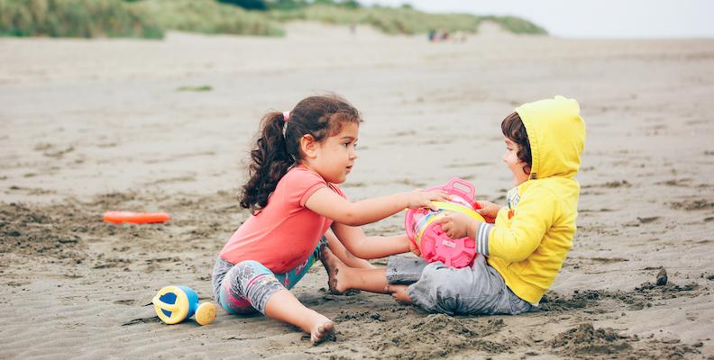 Barn leker på stranden och bråkar om en hink