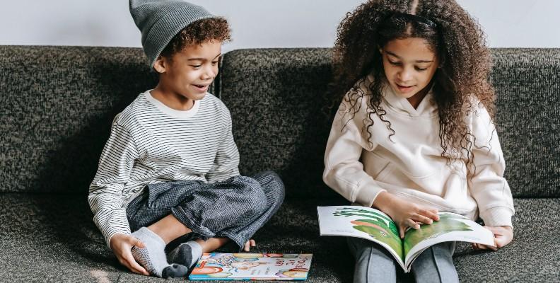 Två barn sitter i en soffa och läser böcker.